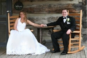 Happy bride and groom sitting on rocking chairs on the porch of their cabin.