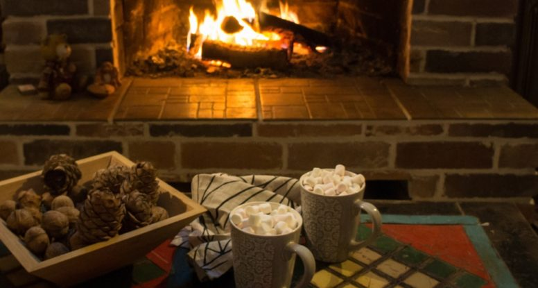 Two cups of hot cocoa by the fireplace