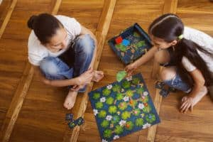 A mother and daughter play a boardgame together