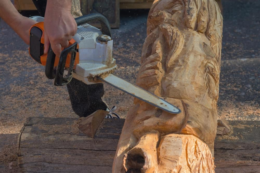 man using a chainsaw to carve